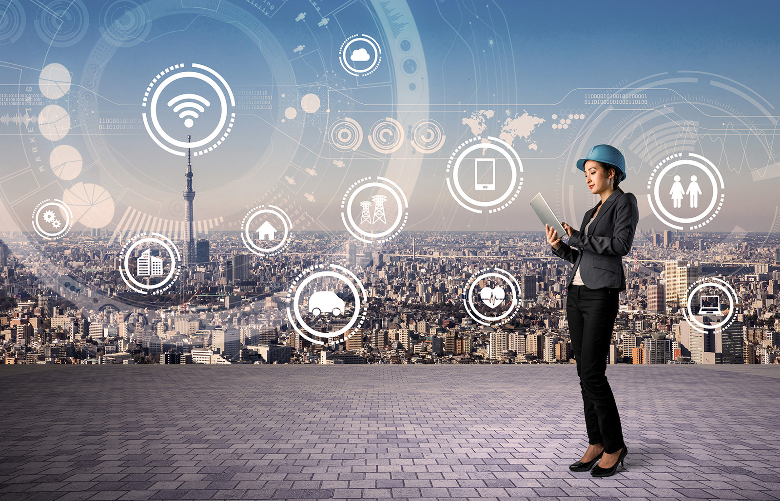 Business woman in a hardhat in front of a cityscape with icons of energy sources