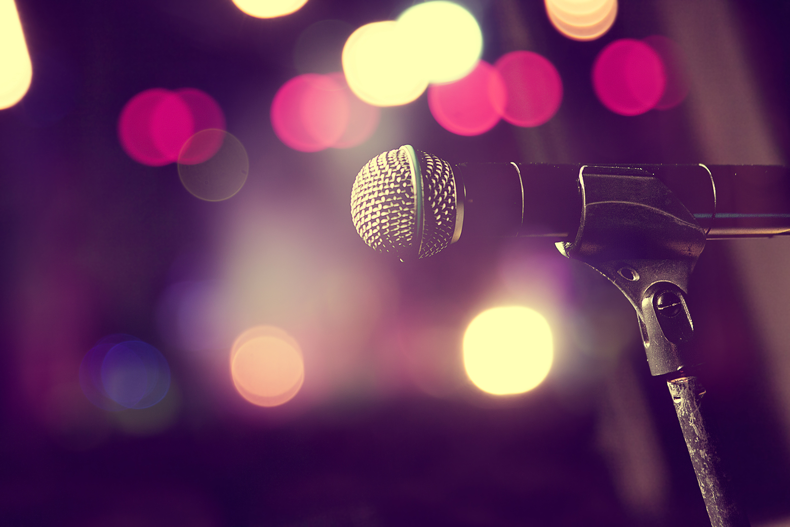 Microphone in front of hazy bokeh stage lights