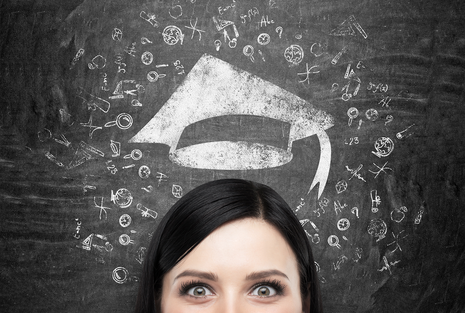 A head of young brunette lady who is thinking about university education. Drawn educational icons and a graduation hat on the black chalkboard background .
