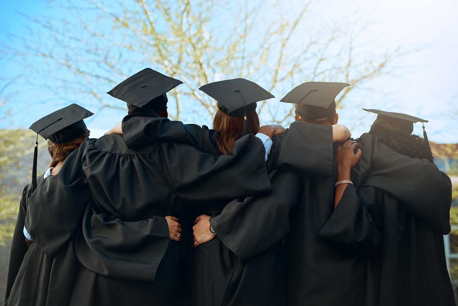 Rearview shot of a group of young students embracing on graduation day