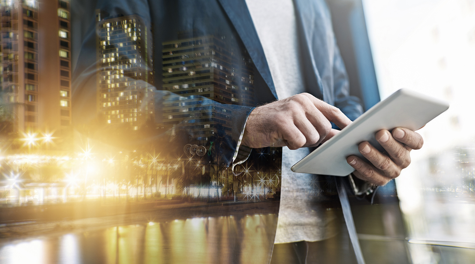 Man reading digital tablet, cityscape in foreground